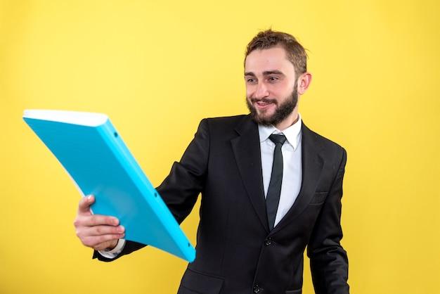 Lächelnder männlicher manager, der sein erfolgreiches projekt mit stolz auf gelb liest