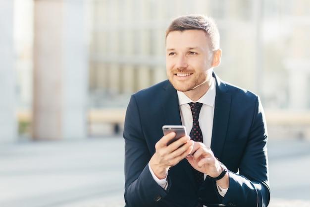 Lächelnder männlicher manager mit dem anziehenden blick, formal gekleidet und benutzt modernes intelligentes telefon