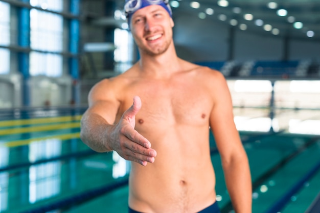 Lächelnder männlicher schwimmer, der seine hand gibt