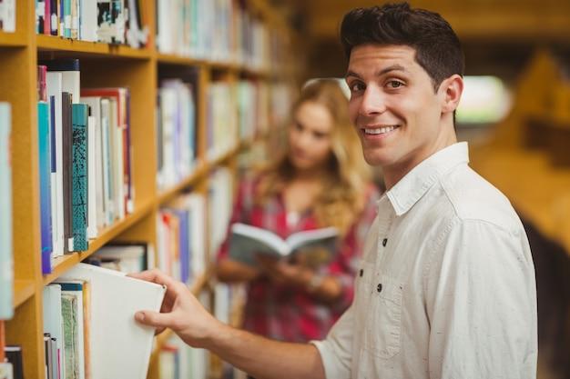Lächelnder männlicher student, der buch in der bibliothek nimmt