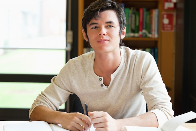 Lächelnder männlicher student, der einen aufsatz schreibt