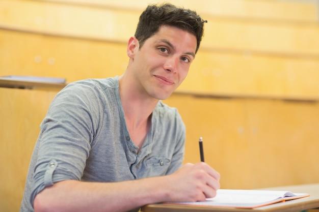 Lächelnder männlicher student während der klasse am vorlesungssal