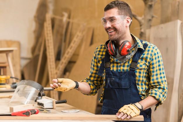 Lächelnder männlicher tischler bei der arbeit in der werkstatt