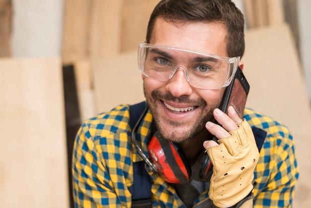 Lächelnder männlicher tischler, der auf smartphone spricht