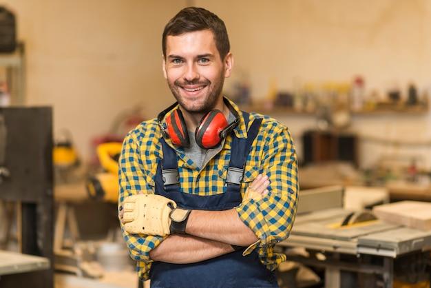 Lächelnder männlicher tischler, der in der werkstatt steht