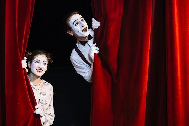 Lächelnder männlicher und weiblicher pantomimekünstler, der vom roten vorhang späht