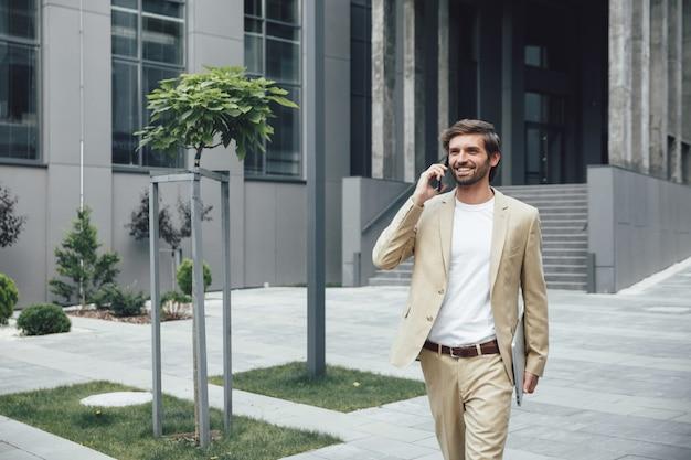 Lächelnder männlicher unternehmer im geschäftsanzug, der auf straße mit tragbarem laptop geht und auf modernem smartphone spricht