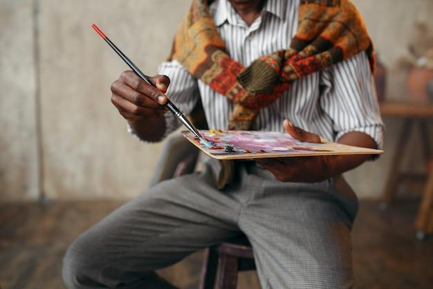 Lächelnder maler mit pinsel und palette an der staffelei