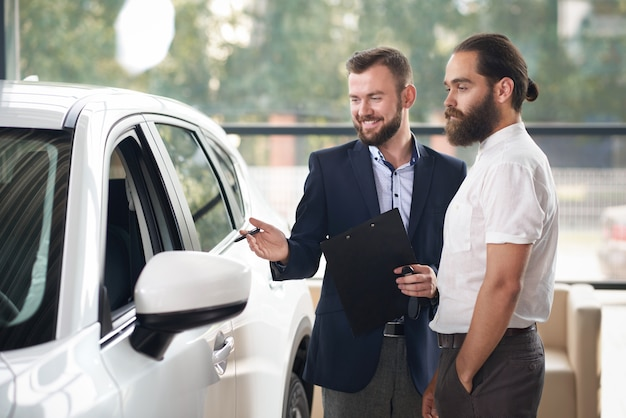 Lächelnder manager der automitte darstellend zum groben mannauto.