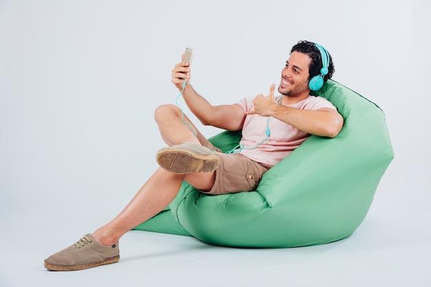 Lächelnder mann auf couch nehmen selfie mit smartphone