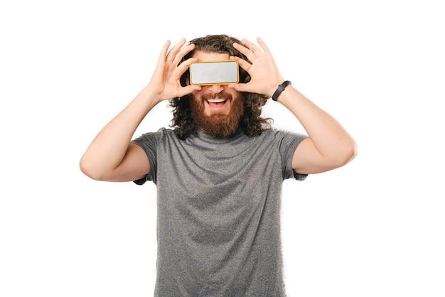 Lächelnder mann bedeckt seine augen mit smartphone über weißem hintergrund.