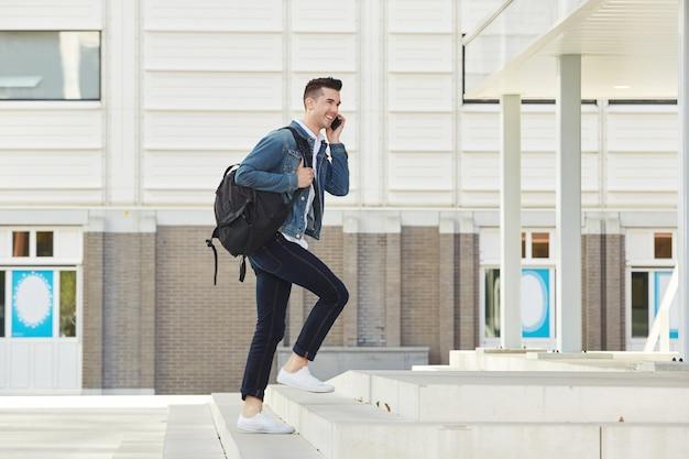 Lächelnder mann beim telefonanruf mit rucksack draußen