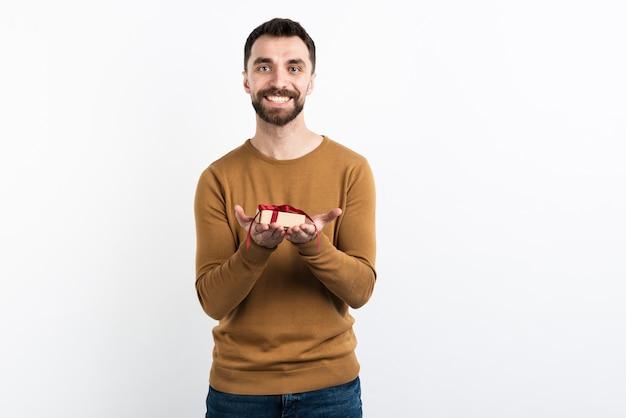 Lächelnder mann bietet geschenk