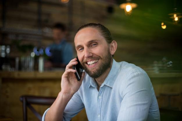 Lächelnder mann, der am handy am kaffee spricht