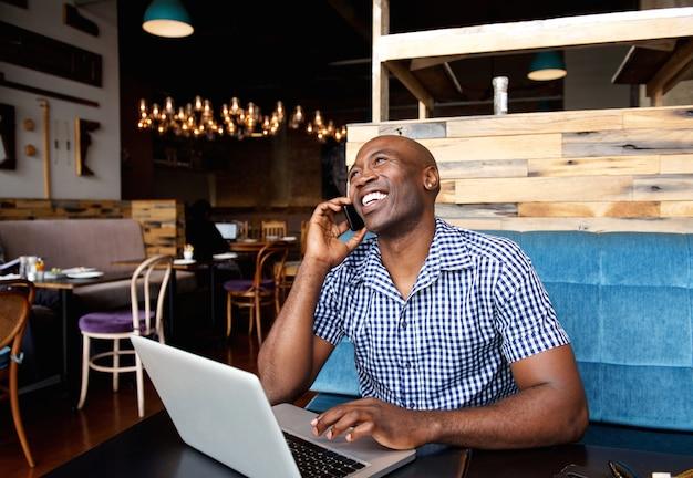 Lächelnder mann, der am handy beim sitzen am café mit laptop spricht