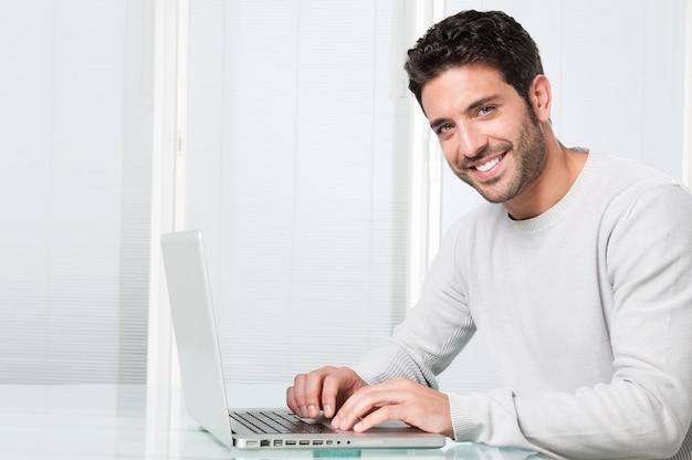 Lächelnder mann, der am laptop arbeitet