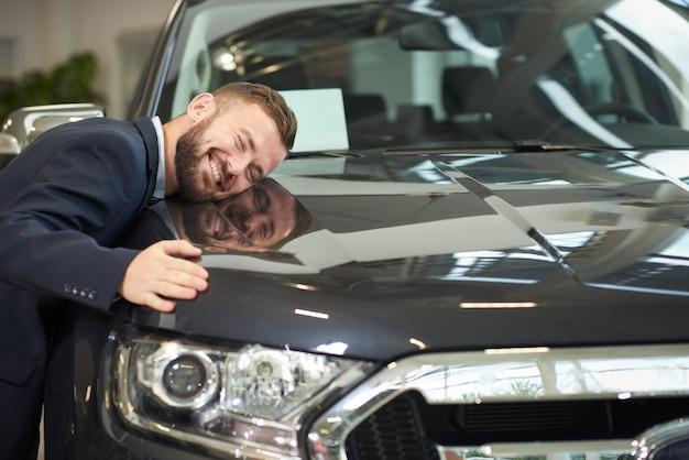 Lächelnder mann, der auf autohaube liegt und auto umarmt.