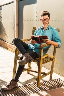 Lächelnder mann, der auf dem holzstuhl liest das buch sitzt
