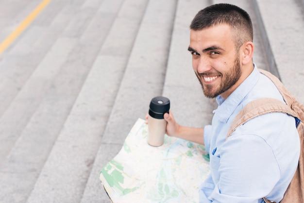 Lächelnder mann, der auf dem treppenhaus hält die karte und wegwerfschale betrachtet kamera sitzt