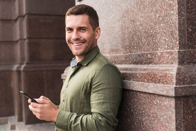 Lächelnder mann, der auf der wand hält mobiltelefon sich lehnt und kamera betrachtet