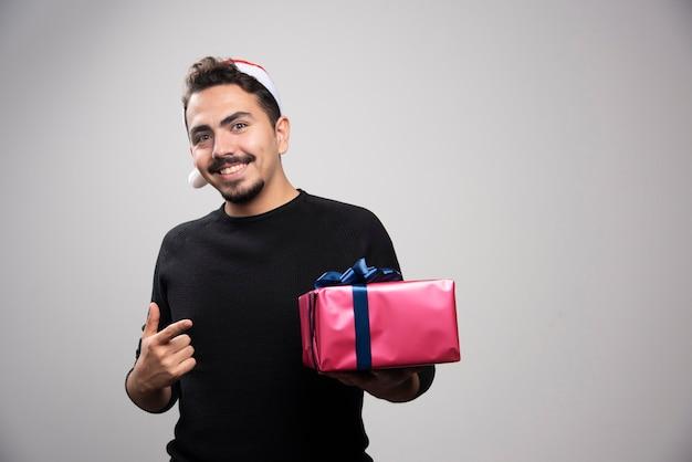 Lächelnder mann, der auf eine geschenkbox über einer grauen wand zeigt.