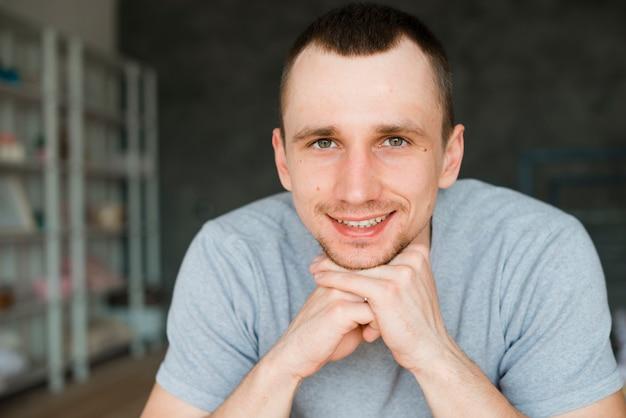 Lächelnder mann, der auf faust sich lehnt und kamera betrachtet