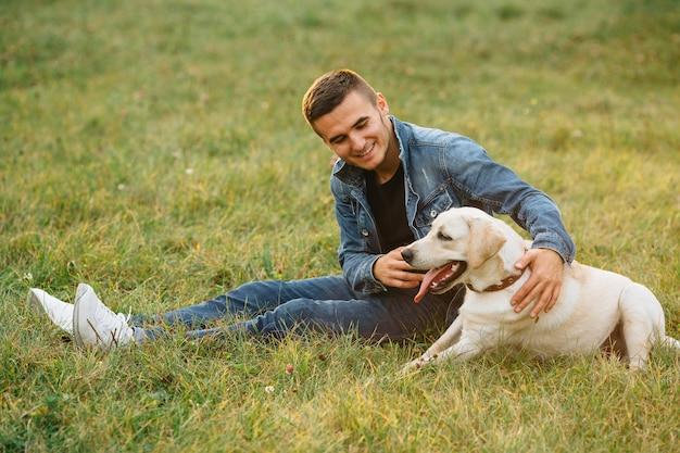 Lächelnder mann, der auf gras mit seinem hund labrador im park sitzt