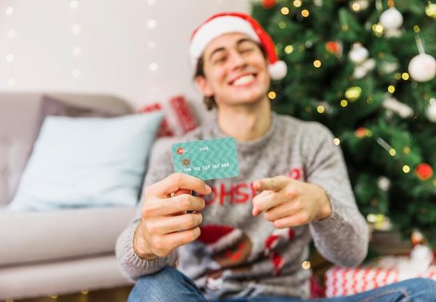 Lächelnder mann, der auf kreditkarte zeigt