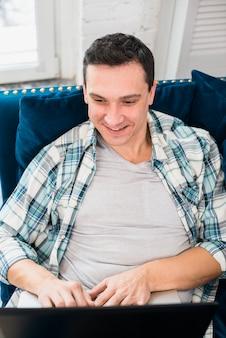 Lächelnder mann, der auf laptop schreibt und auf sofa sitzt
