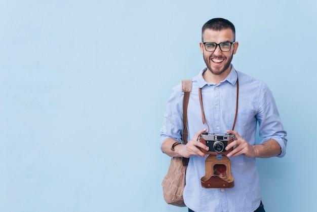 Lächelnder mann, der auge beim halten der kamera steht gegen blauen hintergrund blinzelt
