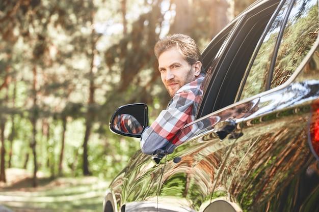 Lächelnder mann, der aus dem fenster schaut, während er mit der familie unterwegs ist