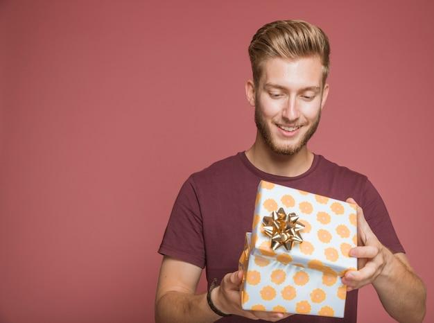 Lächelnder mann, der blumengeschenkbox mit goldenem bogen öffnet
