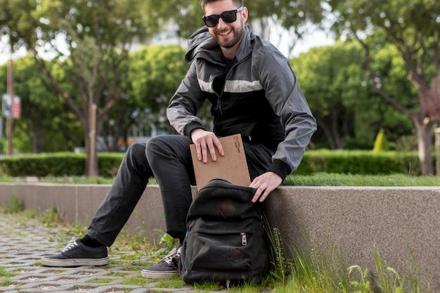 Lächelnder mann, der buch in rucksack einsetzt