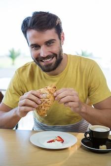 Lächelnder mann, der croissant im kaffeehaus hat
