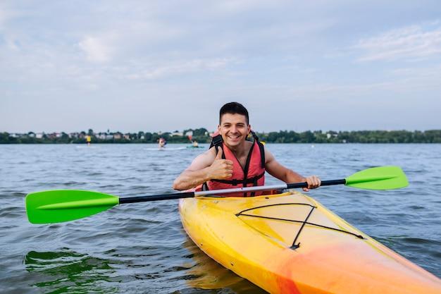 Lächelnder mann, der daumen herauf zeichen beim kayak fahren zeigt