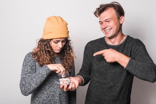 Lächelnder mann, der den finger auf die kranke frau nimmt pillen von der hand zeigt