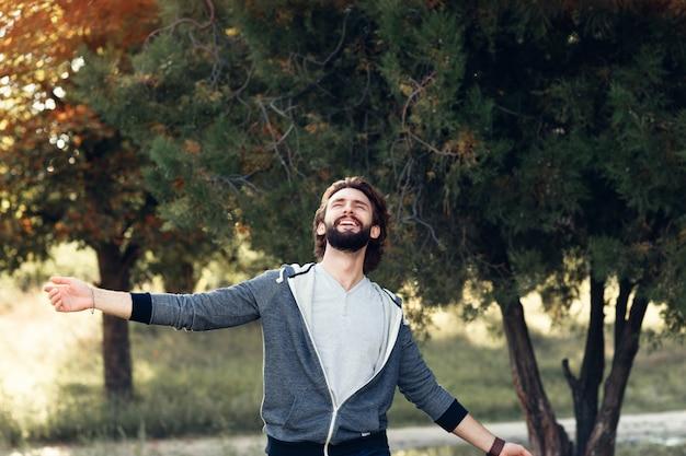 Lächelnder mann, der den wind genießt, der im wald weht.