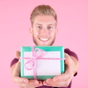 Lächelnder mann, der die eingewickelte geschenkbox gebunden mit rosa schnur anbietet