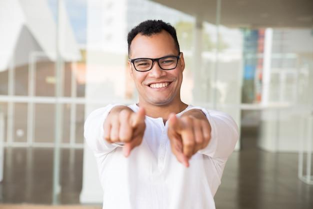 Lächelnder mann, der die kamera, zeigend auf die kamera mit den händen betrachtet