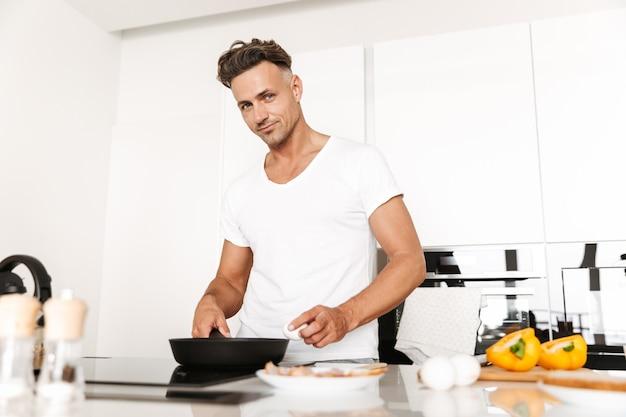 Lächelnder mann, der eier zum frühstück kocht