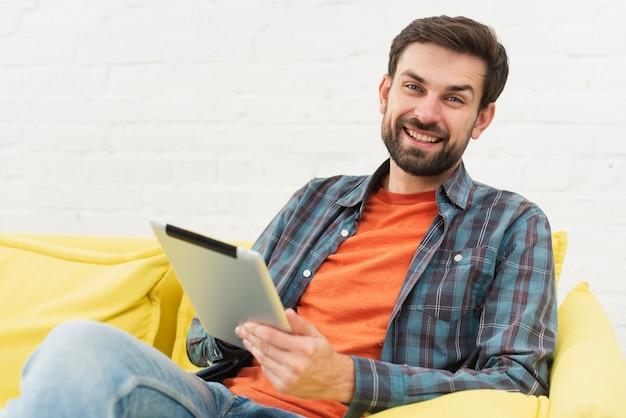 Lächelnder mann, der eine tablette hält