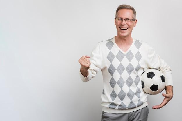 Lächelnder mann, der einen fußball mit kopieraum hält