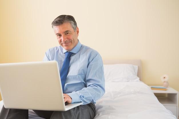 Lächelnder mann, der einen laptop sitzt auf bett verwendet