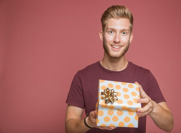 Lächelnder mann, der eingewickelte geschenkbox gegen farbigen hintergrund hält