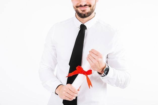 Lächelnder mann der ernte mit diplom