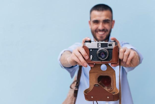 Lächelnder mann, der foto mit der retro- kamera steht gegen blaue wand macht