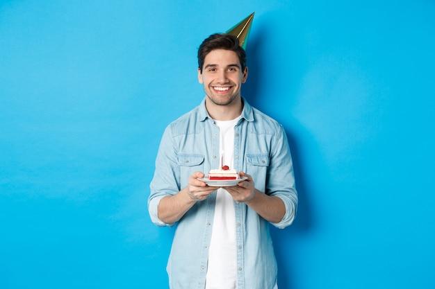 Lächelnder mann, der geburtstagskuchen hält und geburtstagsfeierhut trägt und über blauem hintergrund feiert.