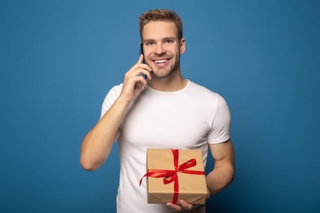 Lächelnder mann, der geschenk hält und auf smartphone lokalisiert auf blau spricht