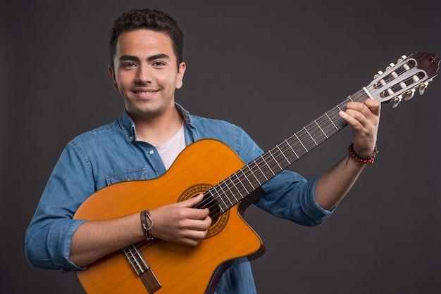 Lächelnder mann, der gitarre auf dunklem hintergrund spielt. hochwertiges foto