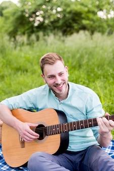 Lächelnder mann, der gitarre auf picknick spielt